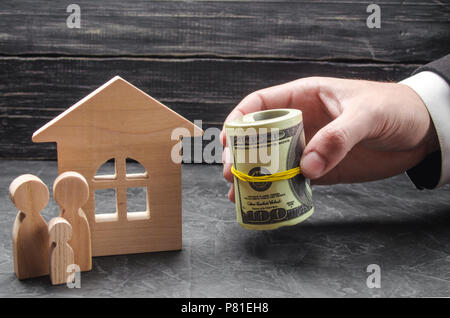 The hand of a businessman extends money to a wooden house. The family is standing near the house. The concept of buying and housing. Compensation and  - Stock Photo