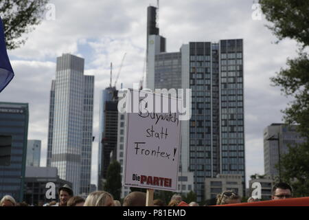 Frankfurt, Germany. 07th July, 2018. A protester holds a sign that reads 'Baywatch instead of Frontex!' with the Frankfurt skyline in the background. Around 800 protesters marched through Frankfurt to protest against the politics of the German government and the EU of closed borders and the prevention of sea rescue operations of NGOs, by grounding their ships in Malta, that causes refugees to drown in the Mediterranean. They called for the Mayor of Frankfurt to declare Frankfurt a safe haven city for refugees from the Mediterranean. The protest was part of the German wide Seebrucke (Sea bridge - Stock Photo