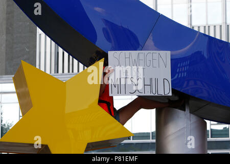 Frankfurt, Germany. 07th July, 2018. A protester has climbed the large Euro sign outside the former seat of the ECB and holds a sign that reads 'Silence means complicity'. Around 800 protesters marched through Frankfurt to protest against the politics of the German government and the EU of closed borders and the prevention of sea rescue operations of NGOs, by grounding their ships in Malta, that causes refugees to drown in the Mediterranean. They called for the Mayor of Frankfurt to declare Frankfurt a safe haven city for refugees from the Mediterranean. The protest was part of the German wide - Stock Photo