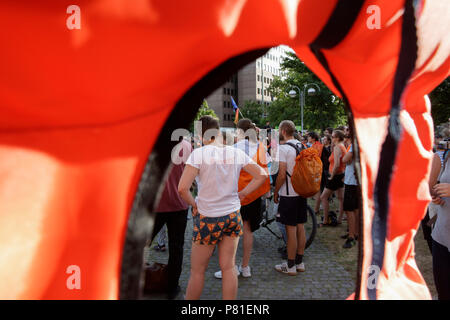 Frankfurt, Germany. 07th July, 2018. People at the protest seen through a life vest. Around 800 protesters marched through Frankfurt to protest against the politics of the German government and the EU of closed borders and the prevention of sea rescue operations of NGOs, by grounding their ships in Malta, that causes refugees to drown in the Mediterranean. They called for the Mayor of Frankfurt to declare Frankfurt a safe haven city for refugees from the Mediterranean. The protest was part of the German wide Seebrucke (Sea bridge) protest that saw thousands of people protest in several German  - Stock Photo
