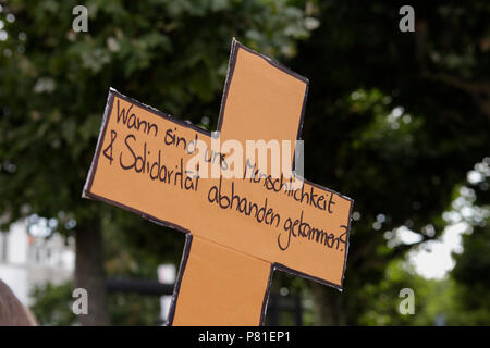 Frankfurt, Germany. 07th July, 2018. A protester carries a cross that reads 'When did we loose humanity and solidarity?'. Around 800 protesters marched through Frankfurt to protest against the politics of the German government and the EU of closed borders and the prevention of sea rescue operations of NGOs, by grounding their ships in Malta, that causes refugees to drown in the Mediterranean. They called for the Mayor of Frankfurt to declare Frankfurt a safe haven city for refugees from the Mediterranean. The protest was part of the German wide Seebrucke (Sea bridge) protest that saw thousands - Stock Photo