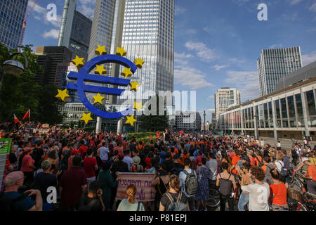 Frankfurt, Germany. 07th July, 2018. Protesters have assembled at the large Euro sign outside the former seat of the ECB. Around 800 protesters marched through Frankfurt to protest against the politics of the German government and the EU of closed borders and the prevention of sea rescue operations of NGOs, by grounding their ships in Malta, that causes refugees to drown in the Mediterranean. They called for the Mayor of Frankfurt to declare Frankfurt a safe haven city for refugees from the Mediterranean. The protest was part of the German wide Seebrucke (Sea bridge) protest that saw thousands - Stock Photo