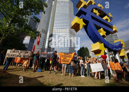 Frankfurt, Germany. 07th July, 2018. Protesters pose with banners and signs at the large Euro sign outside the former seat of the ECB. Around 800 protesters marched through Frankfurt to protest against the politics of the German government and the EU of closed borders and the prevention of sea rescue operations of NGOs, by grounding their ships in Malta, that causes refugees to drown in the Mediterranean. They called for the Mayor of Frankfurt to declare Frankfurt a safe haven city for refugees from the Mediterranean. The protest was part of the German wide Seebrucke (Sea bridge) protest that  - Stock Photo