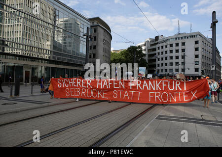 Frankfurt, Germany. 07th July, 2018. Protesters carry a banner that reads 'Safe haven Frankfurt - Seebrucke (Sea bridge) instead of FRONTEX' through Frankfurt. Around 800 protesters marched through Frankfurt to protest against the politics of the German government and the EU of closed borders and the prevention of sea rescue operations of NGOs, by grounding their ships in Malta, that causes refugees to drown in the Mediterranean. They called for the Mayor of Frankfurt to declare Frankfurt a safe haven city for refugees from the Mediterranean. The protest was part of the German wide Seebrucke ( - Stock Photo