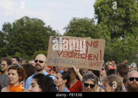 Frankfurt, Germany. 07th July, 2018. A protester holds a sign that reads 'Sea rescue is no crime! Seebrucke instead of Horst', referring to the German Federal minster for the Interior Horst Seehofer. Around 800 protesters marched through Frankfurt to protest against the politics of the German government and the EU of closed borders and the prevention of sea rescue operations of NGOs, by grounding their ships in Malta, that causes refugees to drown in the Mediterranean. They called for the Mayor of Frankfurt to declare Frankfurt a safe haven city for refugees from the Mediterranean. The protest - Stock Photo