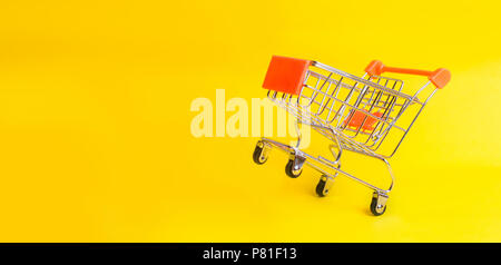 The supermarket cart stands on a yellow background. The concept of shopping and marketing, commerce and trade. The buying mood of people. Statistical  - Stock Photo