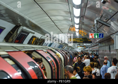 Crowded London Underground station platform and train, Tottenham Court Road tube station busy with passengers at peak time. Packed - Stock Photo