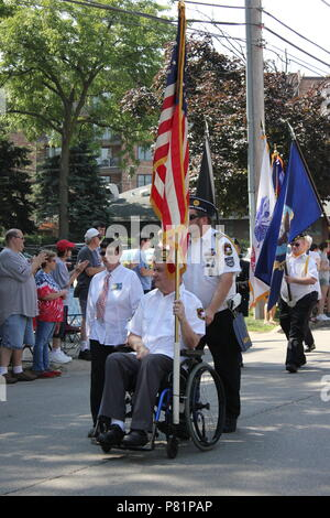 American Flag carried by war veterans in the Fourth of July Parade in Des Plaines, Illinois. - Stock Photo