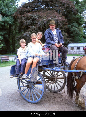 Children on horse-trap in gardens of Muckross House, Killarney National Park, County Kerry, Munster Province, Republic of Ireland - Stock Photo