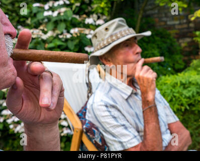Close up of two senior men sitting in deck chairs in a Summer garden  enjoying smoking a Cuban cigar, London, England, UK - Stock Photo