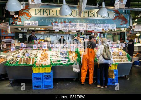 Fish merchants selling fish at Pike Place market, historic and iconic covered market of Seattle, WA, USA. - Stock Photo