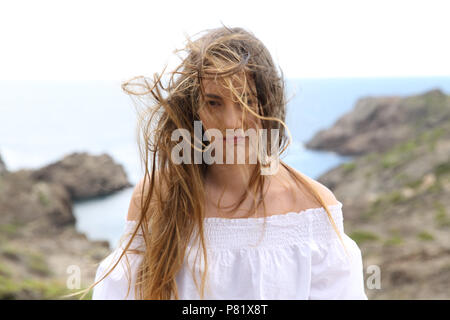 Front view portrait of a frustrated girl with tangled hair due to the wind looking at camera - Stock Photo