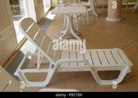 White plastic beach chair is inside the luxurious swimming pool - Stock Photo