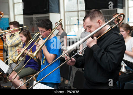 STAFFORD, Va. (April 12, 2016) Musician 1st Class Ben Ford, of Coatesville, Pa., plays trombone alongside students at Colonial Forge High School. MU1 Ford is a member of the U.S. Navy Band Commodores jazz ensemble, which provides educational outreach to young musicians throughout the year. - Stock Photo