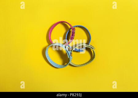 set of belt bracelets on a yellow background - Stock Photo