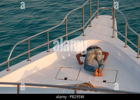 member of the crew praying on knees on the deck, diving cruise, Red Sea, Egypt - Stock Photo