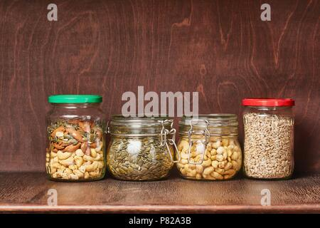 Nuts and seeds in jars in the pantry - Stock Photo