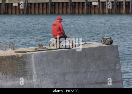 Angler at Weymouth Harbour, Dorset, UK.  1st August 2017. UK Weather. Angler fishing at Weymouth Harbour in the sunshine. Weymouth, Dorset, UK. - Stock Photo