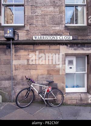 EDINBURGH, SCOTLAND - JUNE 23rd 2018: A bike leans on a wall on Warriston's Close in Edinburgh. - Stock Photo