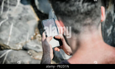Young man using cell phone to send text message - Stock Photo