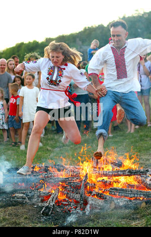 KYIV, UKRAINE - JULY 6, 2018: People jump over the flames of bonfire during the traditional Slavic celebration of Ivana Kupala holiday in Pirogovo ope - Stock Photo