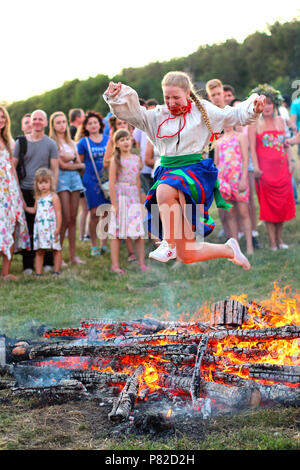 KYIV, UKRAINE - JULY 6, 2018: Young girl in national clothing jumps over the flames of bonfire during the traditional Slavic celebration of Ivana Kupa - Stock Photo
