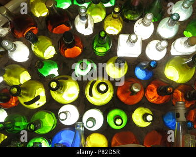 An aerial view of an array of multi-coloured empty wine and beer glass bottles - Stock Photo