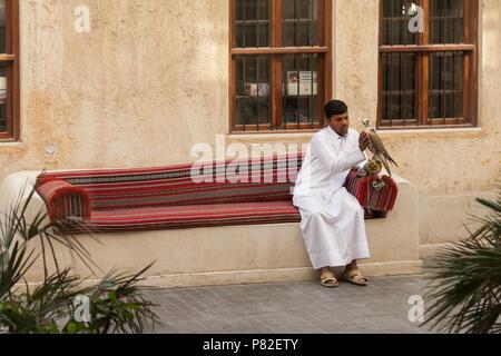 Young man holding a falcon in Souq Waqif, Doha, Qatar - Stock Photo