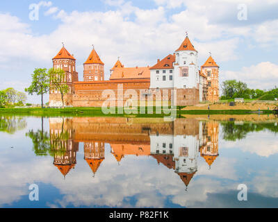 Mir, Belarus. Castle Complex Mir reflected in lake On Sunny Day with blue sky Background. Old medieval Towers and walls of traditional fort from unesco world heritage list - Stock Photo