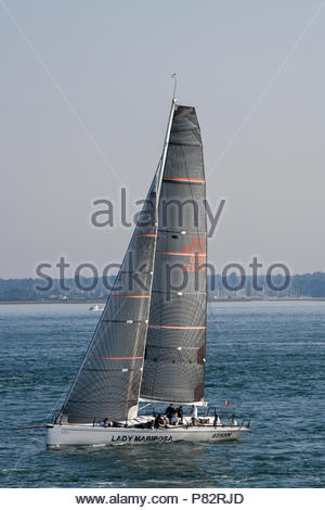 Racing yachts taking part in the annual Round the Island Race off the coast of the Isle of Wight on a hot summers day with very little wind. - Stock Photo