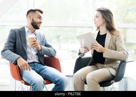 Two Modern Business People Relaxing in Chairs - Stock Photo