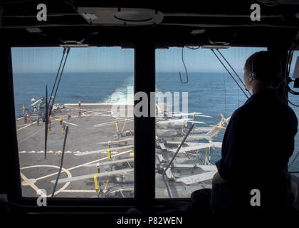 PACIFIC OCEAN (July 20, 2016) – Lt. j.g. Clara Candalor assesses the flight deck for safety hazards while Sailors and Marines conduct a helicopter movement prior to flight operations aboard amphibious transport dock ship USS Somerset (LPD 25). Somerset is participating in PHIBRON-MEU Integrated Training (PMINT), a scenario-based amphibious integration exercise with Amphibious Squadron Five and the 11th Marine Expeditionary Unit as part of the Makin Island Amphibious Ready Group (MKIARG).