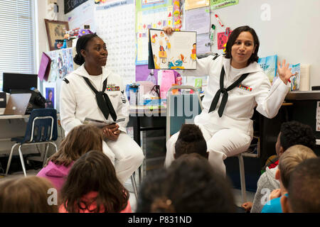 VIRGINIA BEACH, Va. (Oct. 13, 2016) Petty Officer 1st Class Saran McQueen (left) and Petty Officer 1st Class Mariana Carrascomarquez, attached to Navy Expeditionary Combat Command (NECC), read to a third grade class at Shelton Elementary School. Sailors attached to NECC celebrated the Navy's 241st Birthday by volunteering at Shelton Elementary School. - Stock Photo