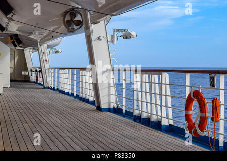 Atlantic Ocean - March 29 2014: Deck onboard Carnival Liberty cruise ship with orange life buoy hanging on side rail. - Stock Photo