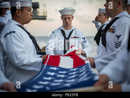 PACIFIC OCEAN (Jan. 17, 2017) Sailors assigned to the aircraft carrier USS Carl Vinson (CVN 70) participate in a burial-at-sea ceremony for 25 U.S. military veterans and one military spouse. The Carl Vinson Strike Group is on a deployment as part of the U.S. Pacific Fleet-led initiative to extend the command and control functions of U.S. 3rd fleet into the Indo-Asia-Pacific region. - Stock Photo