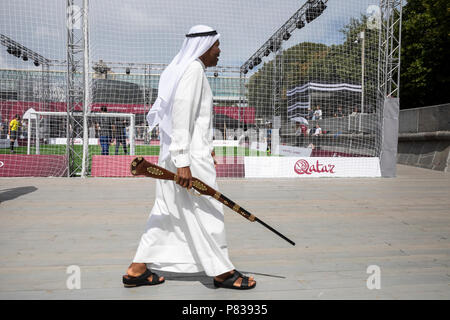 Moscow, Russia. 8th July, 2018. A man with rifle goes against the background of a football ground near Qatar's World Cup 2022 pavilion on Pushkinskaya Embankment in Gorky Park, in Moscow, Russia Credit: Nikolay Vinokurov/Alamy Live News - Stock Photo