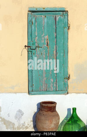 Weathered green wooden shutter on exterior wall of building, Salina Island, Sicily, Italy, Europe - Stock Photo