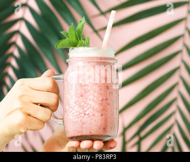 Fands holding a fruit pink smoothie in a glass jar against a decorated pink wall with a palm leaf. Minimalist style. Trend vintage toned. - Stock Photo