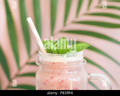 Fruit pink smoothie in a glass jar against a decorated pink wall with a palm leaf. Minimalist style. Trend vintage toned. - Stock Photo