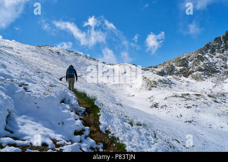 Man hiking through snow in the mountains of the French Alps - Stock Photo