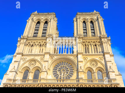Details of French architecture of Notre Dame cathedral of Paris, France. Beautiful sunny day in the blue sky. Our Lady of Paris church. Central main facade with towers and gothic rosettes.