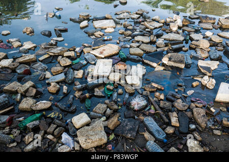 Plastic bottles, polystyrene and other garbage floating in ocean in Negombo, Sri Lanka - Stock Photo