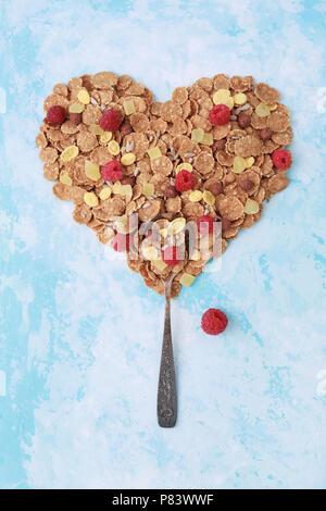 Spoon with heart shape of muesli, corn flakes, raspberries on blue. Healthy eating, breakfast concept. Creative, vertical, minimal. - Stock Photo