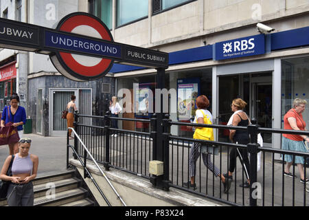 People walk past the branch of the Royal Bank of Scotland bank next to the Notting Hill Gate tube station - Stock Photo