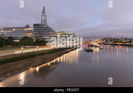 View from Tower Bridge to London Bridge down the River Thames with The Shard, City Hall and HMS Belfast lit up at dawn - Stock Photo