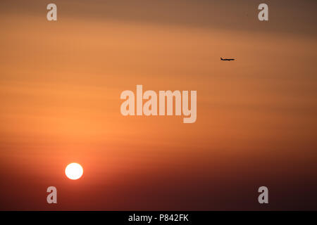 Airplane ( Aeroplane ) passing by a setting sun with gorgeous orange and red sky to its destination, East Attica, Greece, Europe. - Stock Photo