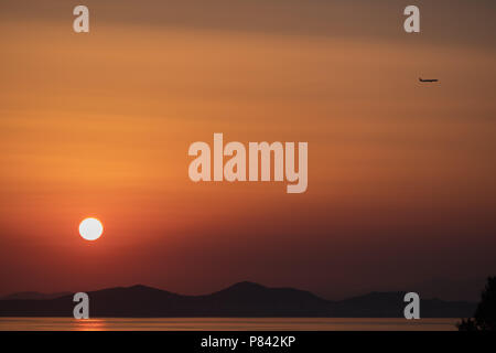 Airplane ( Aeroplane ) passing by a setting sun with gorgeous orange sky and Greek mountain landscape to its destination, East Attica, Greece, Europe. - Stock Photo