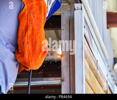 A welder welding a steel pipe to the steel frame of a barn - Stock Photo