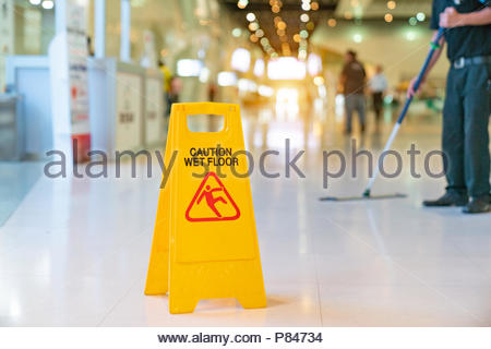 yellow caution wet floor sign - Stock Photo
