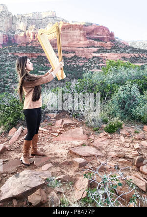 Aeolian Wind Harp raised to the breeze in mystical, red rock desert in Sedona, Arizona. A beautiful young model-released woman plays the instrument - Stock Photo
